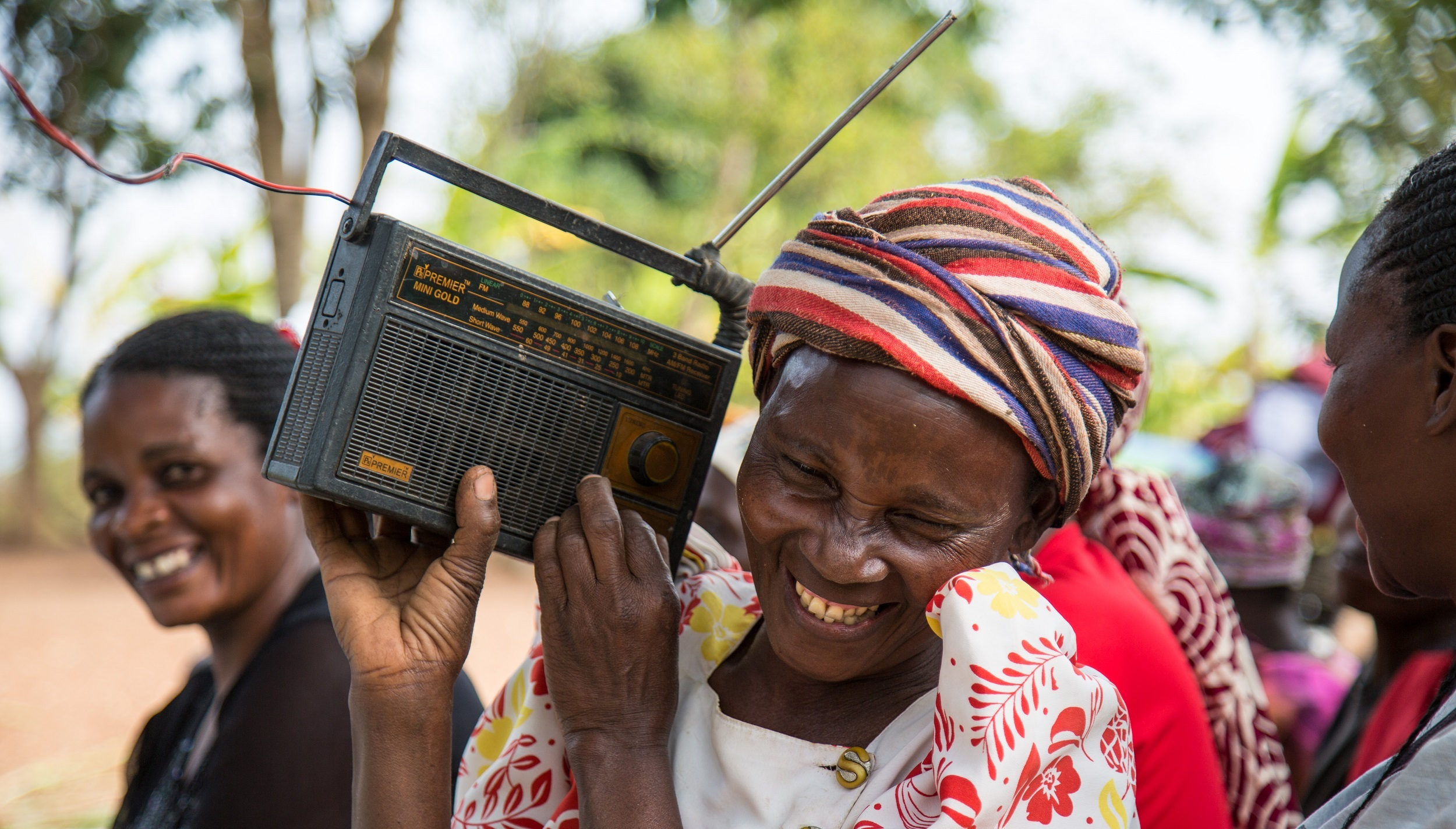 A lady holding a radio up to her ear, smiling
