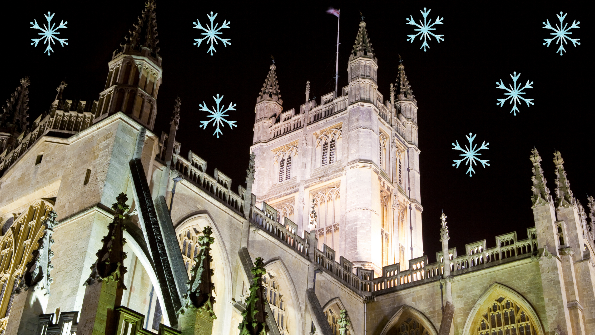 A photo of the Bath Abbey at night, with cartoon snowflakes above