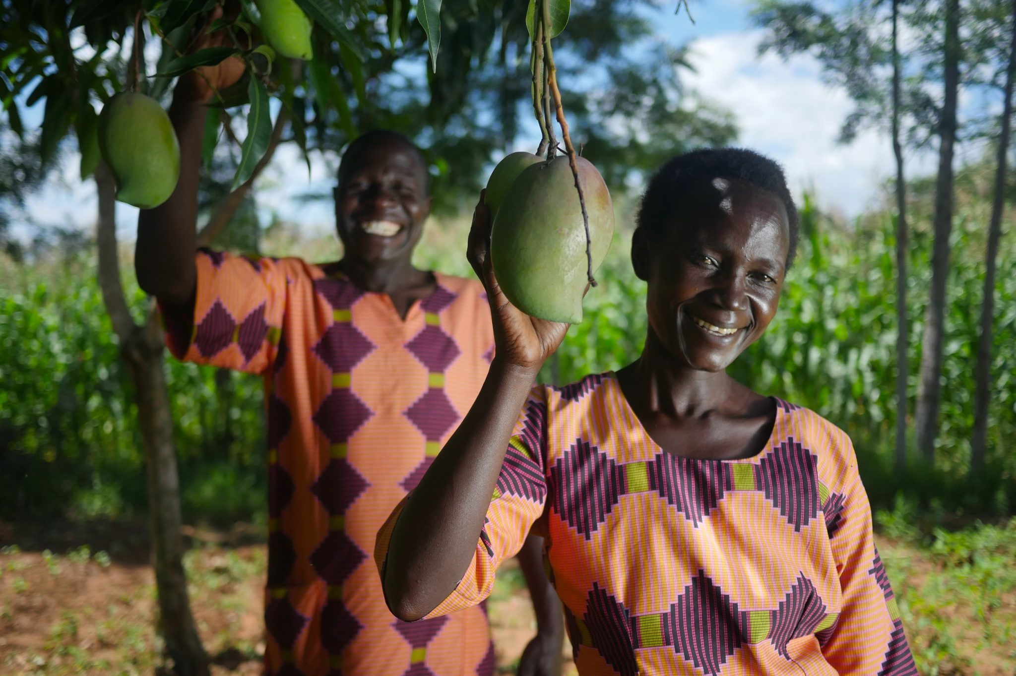 Francis and Josephine smiling holding mangoes from their tree 2048x1363