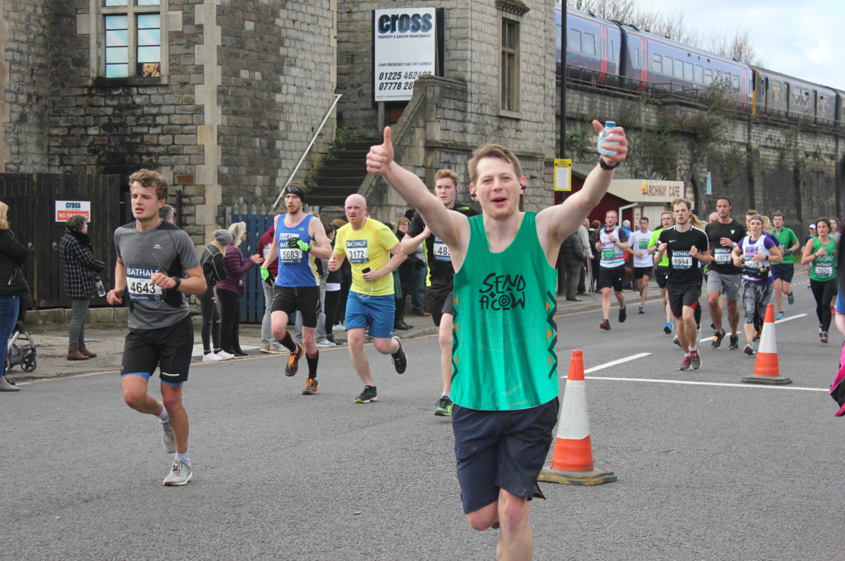 Man wearing a green Send a Cow running top, running with both thumbs up, a crowd behind him
