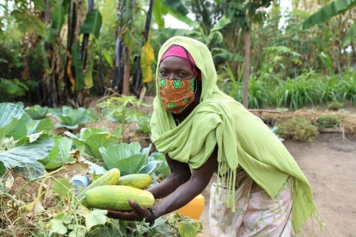 Ruth holding some vegetables in front of her garden, wearing a face mask