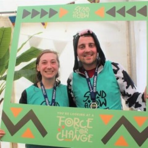 Bath Half runners in the photobooth they hold a sign saying Youre looking at a Force for Change 300x300