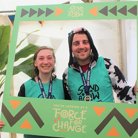 Bath Half runners in the photobooth they hold a sign saying Youre looking at a Force for Change scaled