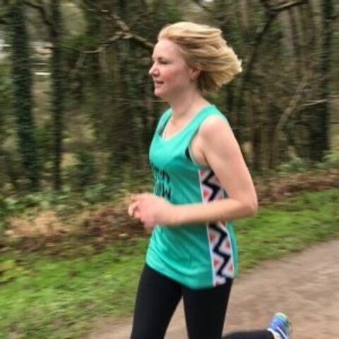 Bath Half runner training woman wearing send a cow running vest running in front of woodland wearing a 300x300