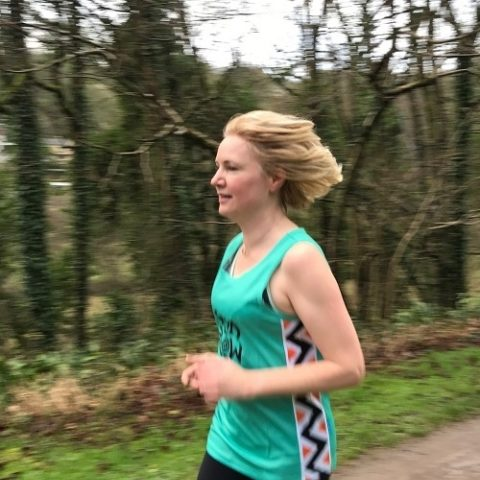 Bath Half runner training woman wearing send a cow running vest running in front of woodland wearing a