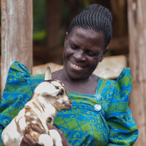 A woman called Edith wearing a green and blue dress holds a baby goat in her arms while smiling