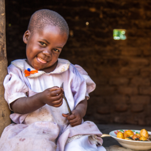 Child smiling with a fork in her hand and bowl of food to her side