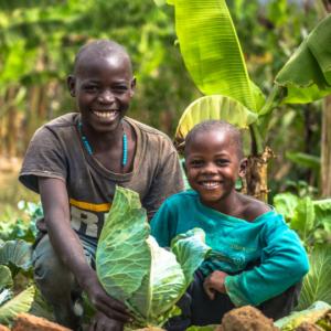 Two children sat down smiling in their vegetable garden