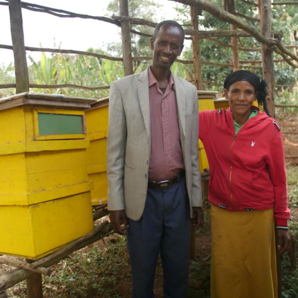 A couple stand in front of their bright yellow beehive smiling