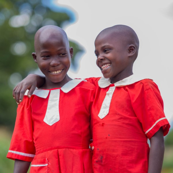 Two children wearing red dresses with their arms around eachother smiling