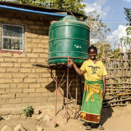 Lontia from Zambia standing in front of her rainwater harvesting tank